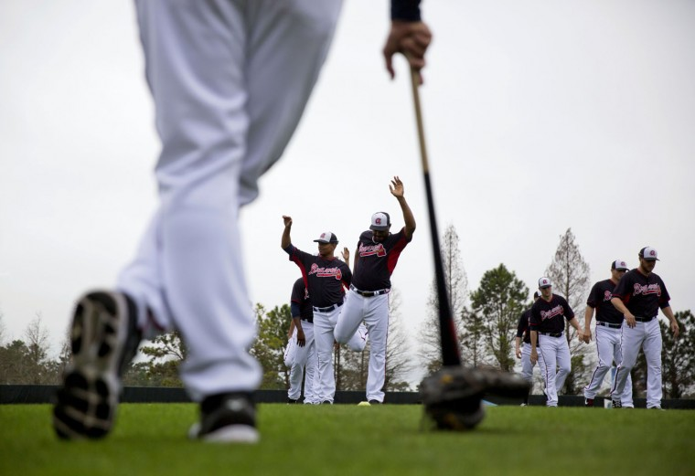 Atlanta Braves' Jose Veras, center right, and Christian Bethancourt, left, stretch as bullpen coach Eddie Perez, front, looks on during a spring training baseball workout, Monday, Feb. 23, 2015, in Kissimmee, Fla. (AP Photo/David Goldman)