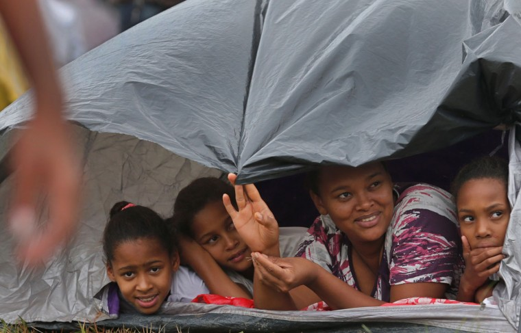 """In this Feb. 7, 2015 photo, Amanda Santana, 39, second from right, and her daughters look out from their makeshift tent at a Homeless Workers Movement squatters camp in the Ceilandia neighborhood of Brasilia, Brazil. Officials say close to 3,000 homeless people have agreed to leave the six areas they occupied over the weekend near and around Brazil's capital city of Brasilia. """"I came to Brasilia over 20 years and i've not been able to find housing,"""" said Santana. """"I work as a maid and on what I earn I can't pay rent. My only hope is to receive government housing.""""(AP Photo/Eraldo Peres)"""