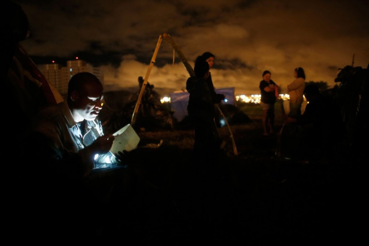 In this Feb. 8, 2015 photo, a man illuminated by the light of a mobile phone has dinner at a Homeless Workers Movement squatters camp in the Ceilandia neighborhood of Brasilia, Brazil. About 3,000 people who are part of the Homeless Workers Movement, which invades lands and buildings in cities across the Brazil, in recent days pitched their paltry shelters on six large tracts of land in and around Brasilia. (AP Photo/Eraldo Peres)