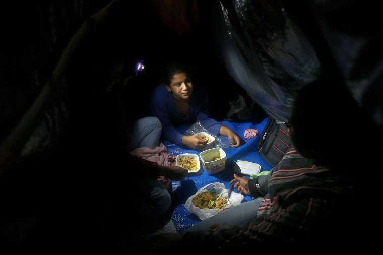 In this Feb. 8, 2015 photo, a family has dinner inside a makeshift tent at a Homeless Workers Movement squatters camp in the Ceilandia neighborhood of Brasilia, Brazil. The family served a humble dinner of rice, vegetables and scraps of chicken meat, all piled into recycled margarine tubs. (AP Photo/Eraldo Peres)