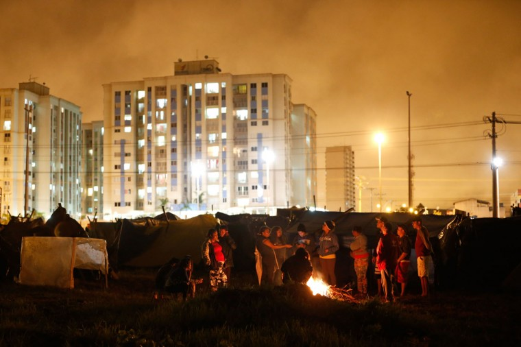 In this Feb. 8, 2015 photo, members of the Homeless Workers Movement warm up beside a bonfire at a squatters camp in the Ceilandia neighborhood in Brasilia, Brazil. Officials say close to 3,000 homeless people gather on rainy nights around the fires to chat and pass the time in as normal fashion as possible. (AP Photo/Eraldo Peres)