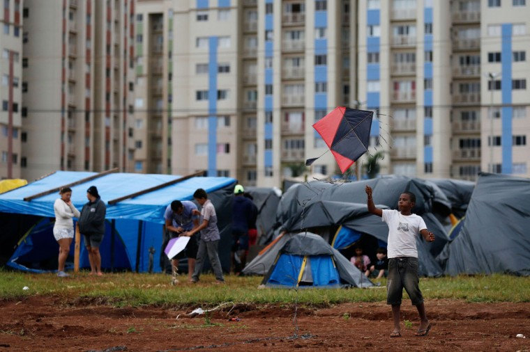 In this Feb. 8, 2015 photo, a boy flies a kite at a Homeless Workers Movement squatters camp in the Ceilandia neighborhood of Brasilia, Brazil. To pass time children fly kites and rough house in their tents made out of black and blue plastic tarps draped over bamboo, while the more fortunate among them have proper tents for protection. The Homeless Workers Movement has agreed to move from the public lands they occupied after authorities agreed to set aside land for low-cost housing projects. (AP Photo/Eraldo Peres)