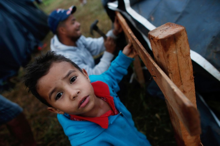 In this Feb. 8, 2015 photo, Luiz Gustavo, 8, helps his father Joaquim Rodrigues, 36, construct a makeshift tent at a Homeless Workers Movement squatters camp in the Ceilandia neighborhood in Brasilia, Brazil. Gustavo, accompanied by his father and mother, is part of a group of about 3,000 people who are part of the Homeless Workers Movement, which invades lands and buildings in cities across the continent-sized nation. (AP Photo/Eraldo Peres)