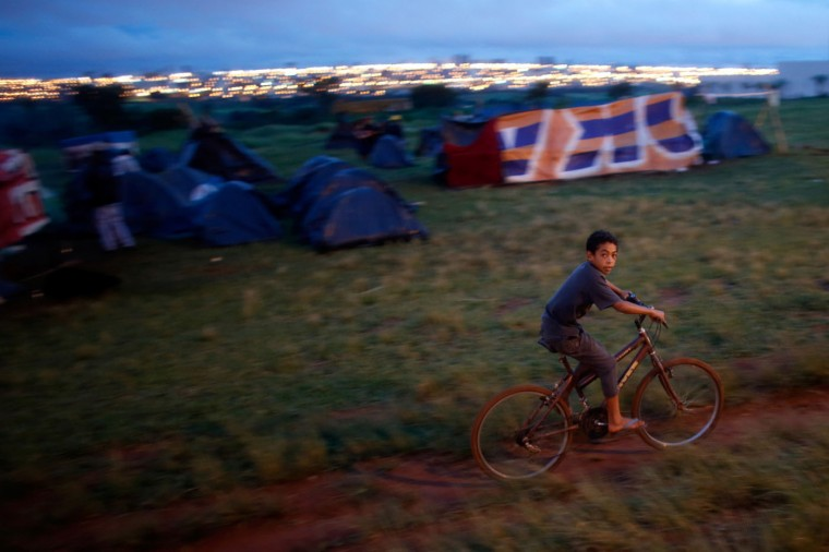 In this Feb. 8, 2015 photo, a boy rides his bike at a Homeless Workers Movement squatters camp in the Ceilandia neighborhood of Brasilia, Brazil. Children on South American summer breaks ride bikes to pass the time and on rainy nights gather with adults around fires to chat. (AP Photo/Eraldo Peres)