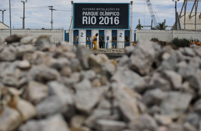 """A worker walks past one of the entrances of the Olympic Park, that reads in Portuguese """"Future facilities of the Olympic Park Rio 2016,"""" in Rio de Janeiro, Brazil, Thursday, Feb. 19, 2015. (AP Photo/Leo Correa)"""