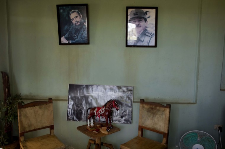 Portraits of Cuba's President Raul Castro, right, and Fidel Castro hang on the wall above a statue of a horse at the state-run Azucarero horse ranch in Artemisa, Cuba. Cuba's tradition of horse breeding and training dates to the 16th century but after the 1959 communist revolution, Fidel Castro's government banned horse racing along with gambling and professional sports. (AP Photo/Ramon Espinosa)