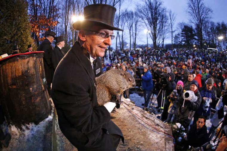 In this photo taken with a fisheye lens, Groundhog Club handler Ron Ploucha holds Punxsutawney Phil, the weather prognosticating groundhog, during the 129th celebration of Groundhog Day on Gobbler's Knob in Punxsutawney, Pa., Monday, Feb. 2, 2015. Phil's handlers said that the groundhog has forecast six more weeks of winter weather. (AP Photo/Gene J. Puskar)