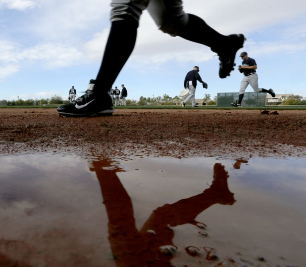 Seattle Mariners players participate in a drill during spring training baseball practice Tuesday, Feb. 24, 2015, in Peoria, Ariz. (AP Photo/Charlie Riedel)
