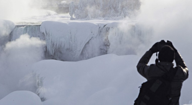 A man photographs ice masses formed around the American Falls as seen from Niagara Falls, Ontario, Canada, Thursday, Feb. 19, 2015. (AP Photo/The Canadian Press,Aaron Lynett)