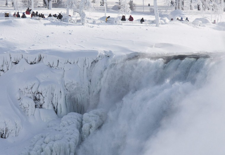 Niagara Falls State Park visitors look over masses of ice formed around the American Falls, photographed from across the Niagara River in Niagara Falls, Ontario, Canada, Thursday, Feb. 19, 2015. (AP Photo/The Canadian Press/Aaron Lynett)