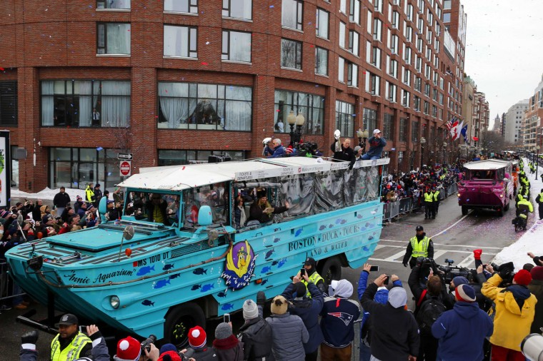 New England Patriots owners Jonathan Kraft, right, and Robert Kraft, left, hold up Lombardi Trophies from a duck boat during a parade in Boston Wednesday, Feb. 4, 2015, to honor the Patriots victory over the Seattle Seahawks in Super Bowl XLIX in Glendale, Ariz. (AP Photo/Winslow Townson)