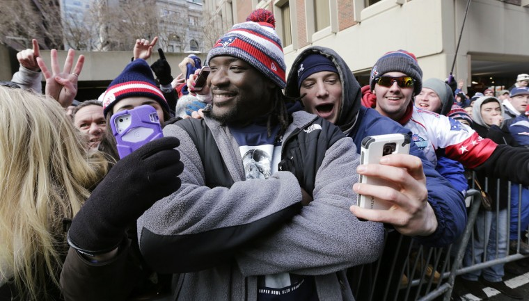 New England Patriots running back LeGarrette Blount poses for selfies with fans as he is congratulated while walking in a parade in Boston, Wednesday, Feb. 4, 2015, to honor the NFL football team's victory over the Seattle Seahawks in Super Bowl XLIX in Glendale, Ariz. (AP Photo/Charles Krupa)