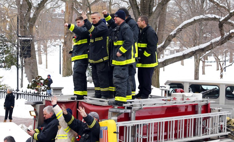 Boston firefighters cheer from the top of a fire truck during a parade in Boston, Wednesday, Feb. 4, 2015, to honor the New England Patriots' victory over the Seattle Seahawks in Super Bowl XLIX in Glendale, Ariz. (AP Photo/Winslow Townson)