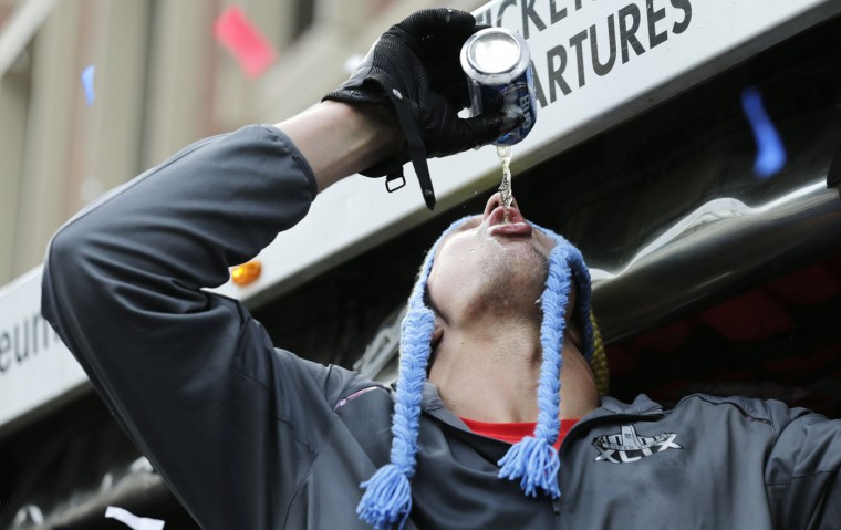 New England Patriots tight end Rob Gronkowski chugs a beer, tossed to him by a fan, during a parade in Boston, Wednesday, Feb. 4, 2015, to honor the NFL football teams victory over the Seattle Seahawks in Super Bowl XLIX in Glendale, Ariz. (AP Photo/Charles Krupa)