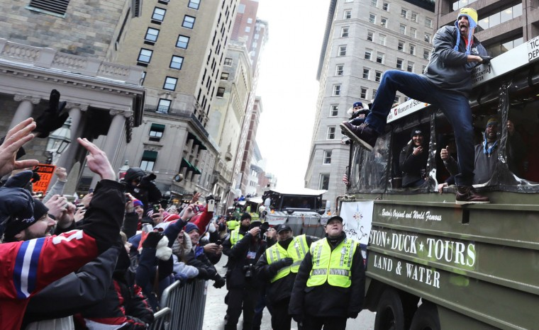New England Patriots tight end Rob Gronkowski, right, hangs out of a duck boat as fans cheer during a parade in Boston, Wednesday, Feb. 4, 2015, to honor the NFL football teams victory over the Seattle Seahawks in Super Bowl XLIX in Glendale, Ariz. (AP Photo/Charles Krupa)