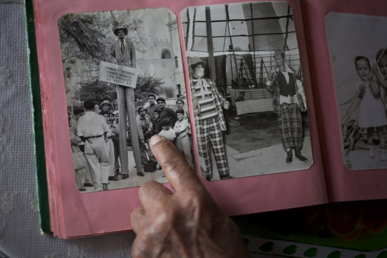 "Veteran clown Ricardo Farfan, popularly known as ""Pitito,"" points to himself standing on stilts in a picture from the 1950's, during his 91st birthday celebration at his home in Lima, Peru. In the center photo, Farfan is the clown at right. Farfan reflected that ""working at the circus allows you to travel the country, meet new people, customs and food."" (AP Photo/Esteban Felix)"
