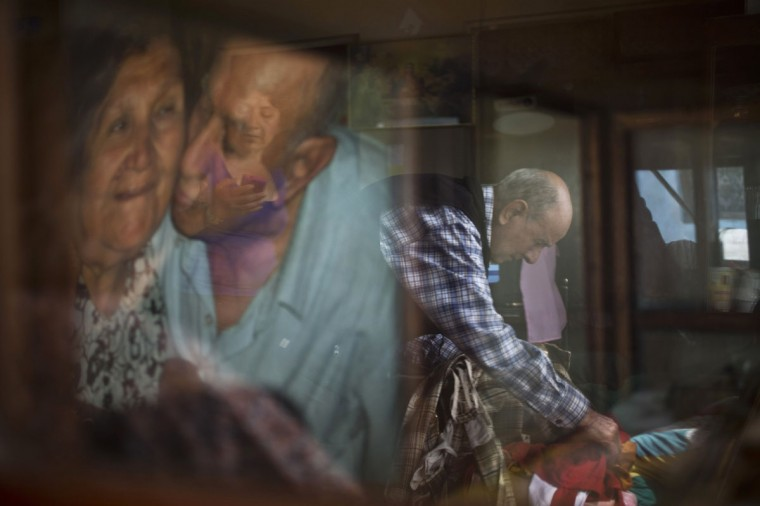"Veteran clown Ricardo Farfan, popularly known as ""Pitito,"" is reflected in a glass case as he prepares his clown costume for his 91st birthday celebration at his home in Lima, Peru. Also reflected in the glass are his daughter Carmen, and a photograph of Farfan kissing his wife Maria Munoz. Farfan took over his father's circus in the 1970's, which Maria managed in addition to painting circus tents and sewing costumes. (AP Photo/Esteban Felix)"