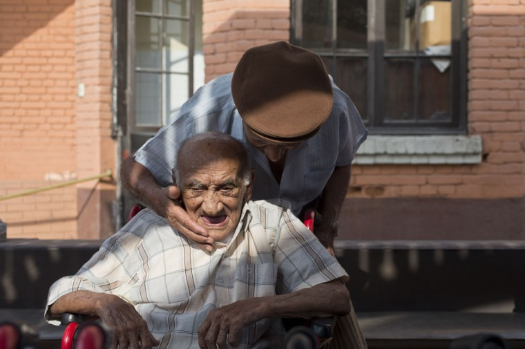 """Veteran clown Ricardo Farfan, popularly known as """"Pitito,"""" top, says goodbye to his friend Emilio Perez who celebrated his 102nd birthday at the nursing home in Lima, Peru. Although Farfan worked his entire life at his family's circus, starting when he was three-years-old in 1927, and ran it for decades to support his family, the government does not give monthly pension payments to circus artists, so his four children support him financially. (AP Photo/Esteban Felix)"""