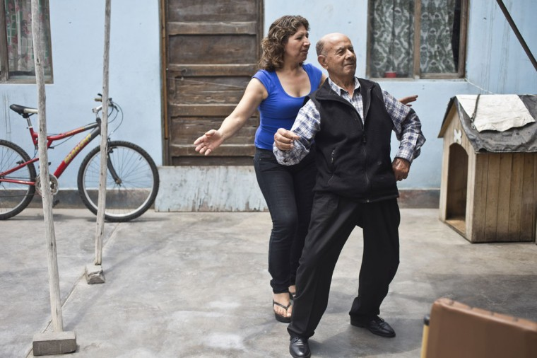 "Veteran clown Ricardo Farfan, popularly known as ""Pitito,"" dances with his daughter Carmen during his 91st birthday party at his home in Lima, Peru. Farfan raised his four children in the circus he inherited from his father. Although none of them took over the circus, his son in Italy performs as a clown on weekends on the side of his car manufacturing job. (AP Photo/Esteban Felix)"