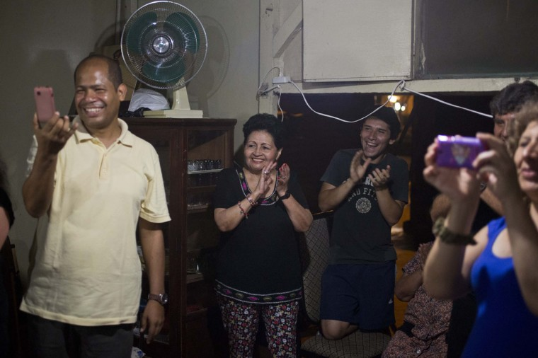 """Relatives and friends of veteran clown Ricardo Farfan, popularly known as """"Pitito,"""" applaud his performance during his 91st birthday party in Lima, Peru. Farfan said he begins his days looking over his old notebook of jokes and openers from his eight decade long circus career. (AP Photo/Esteban Felix)"""