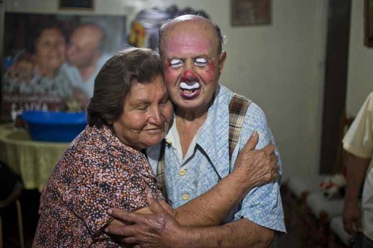 "Veteran clown Ricardo Farfan, popularly known as ""Pitito,"" gets a hug from his wife Maria Munoz after he performed during his 91st birthday party at their home in Lima, Peru. Farfan inherited his father's circus, where he worked since he was three-years-old in 1927, and his wife Maria Munoz managed it. They had to close the circus in 1990 when Maria fell at home and severely damaged her back. (AP Photo/Esteban Felix)"