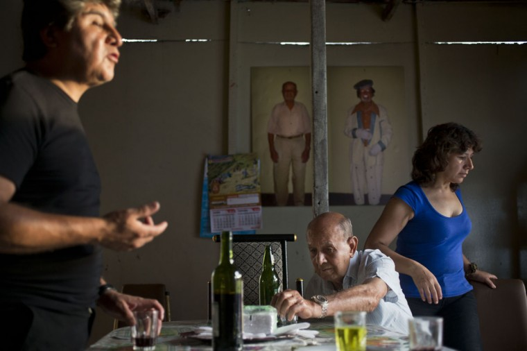 """Veteran clown Ricardo Farfan, popularly known as """"Pitito,"""" center, sits at the table during his 91st birthday celebration at his home with his son Ricardo and daughter Carmen in Lima, Peru. Farfan's other two children live in Italy, and all four of them worked with him at the family circus when they were growing up. Although none of them took over the family circus, his son in Italy performs as a clown on weekends on the side of his car manufacturing job. (AP Photo/Esteban Felix)"""