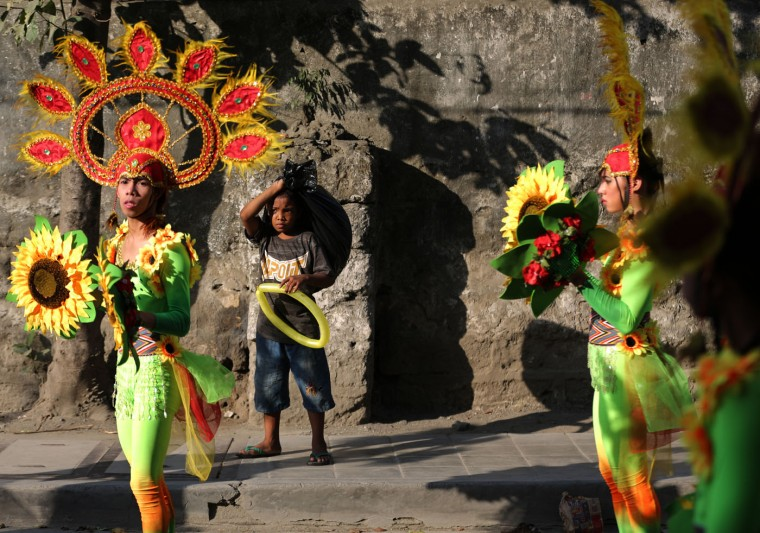 "A boy watches residents dressed as flowers during the start of the annual ""Caracol"" festival in suburban Makati, south of Manila, Philippines on Sunday, Feb. 22, 2015. The event aims to promote public awareness on environmental issues and cultural heritage. (AP Photo/Aaron Favila)"