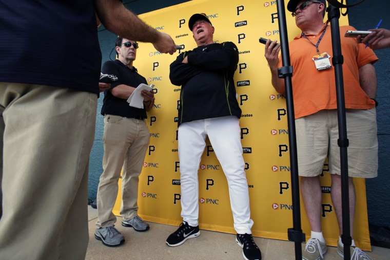 Pittsburgh Pirates manager Clint Hurdle, center, talks with reporters after a spring training baseball workout in Bradenton, Fla., Sunday, Feb. 22, 2015. (AP Photo/Gene J. Puskar)
