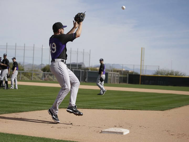 Colorado Rockies' Rex Brothers (49) runs a drill during spring training baseball practice Saturday, Feb. 21, 2015, in Scottsdale, Ariz. (AP Photo/Darron Cummings)
