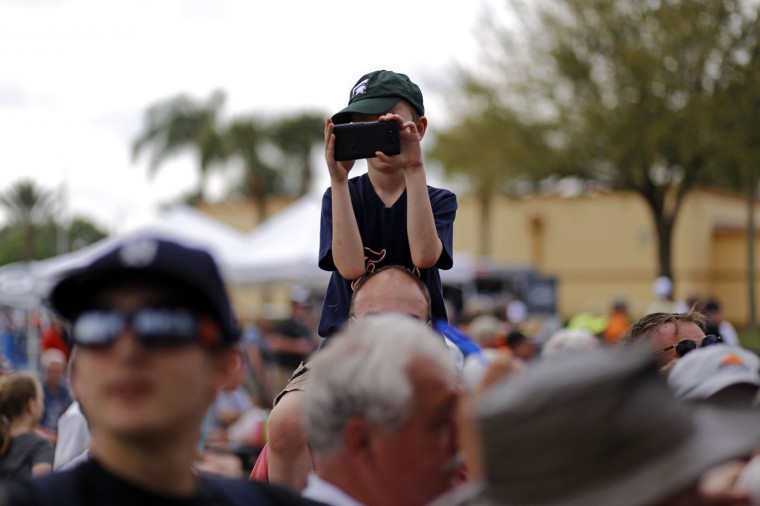 A young Detroit Tigers fan takes photos as players leave the practice field after a spring training baseball workout in Lakeland, Fla., Tuesday, Feb. 24, 2015. (AP Photo/Gene J. Puskar)