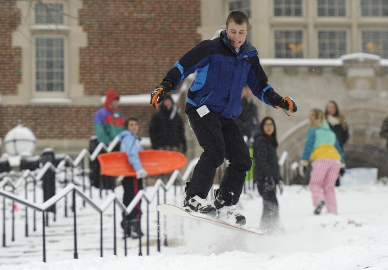 A University of Tennessee student takes a jump while snowboarding down a hill from Ayres Hall, following overnight snows in Knoxville, Tenn., on Tuesday, Feb. 24, 2015. Tennessee Emergency Management Agency officials say 27 people around the state have died as a result of the ice storm and frigid temperatures. (AP Photo/Knoxville News Sentinel, Adam Lau)