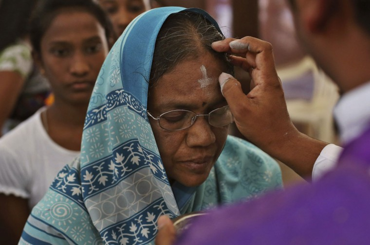 An Indian Catholic priest marks cross symbol on the forehead of devotees during an Ash Wednesday service at the St. Joseph Cathedral in Hyderabad, India, Wednesday, Feb. 18, 2015. (AP Photo/Mahesh Kumar A.)