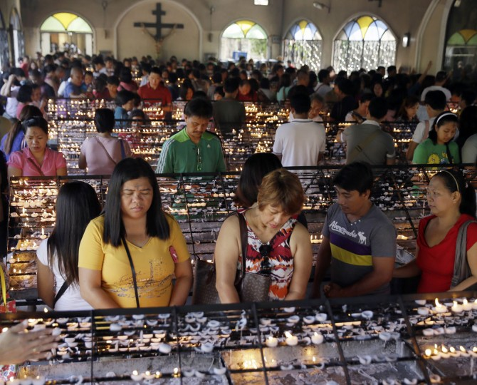 With their foreheads marked with ash, Catholic devotees pray after lighting candles in observance of Ash Wednesday at The Redemptorist Church at suburban Paranaque city, south of Manila, Philippines Wednesday, Feb. 18, 2015. (AP Photo/Bullit Marquez)