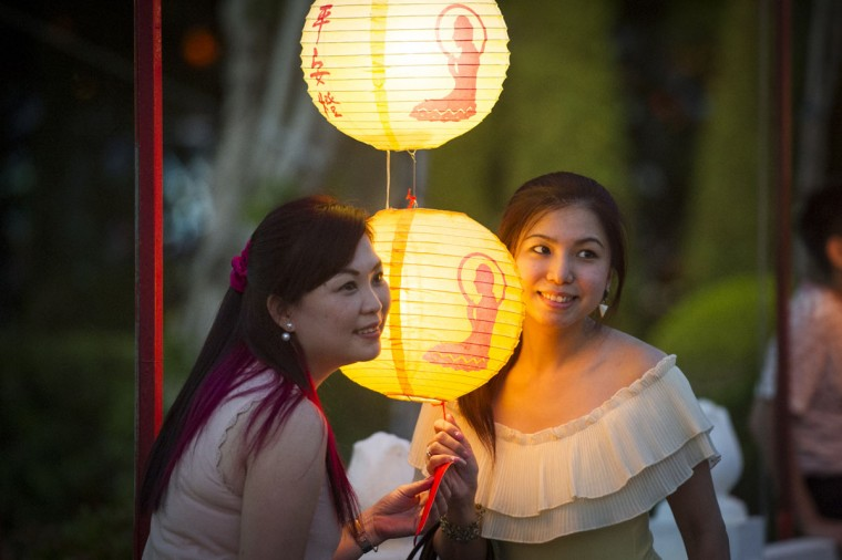 Malaysian ethnic Chinese women have their souvenir photograph taken with traditional Chinese lantern decorations at Fo Guang Shan Dong Zen Buddhist Temple in Jenjarom, outside Kuala Lumpur, Malaysia on Saturday, Feb. 21, 2015. (AP Photo/Joshua Paul)