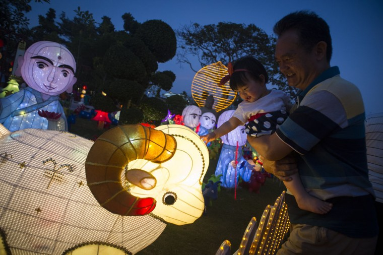 A Malaysian ethnic Chinese child touches an illuminated sheep statue at Fo Guang Shan Dong Zen Buddhist Temple decorated for the Chinese Lunar New Year in Jenjarom, outside Kuala Lumpur, Malaysia on Saturday, Feb. 21, 2015. (AP Photo/Joshua Paul)