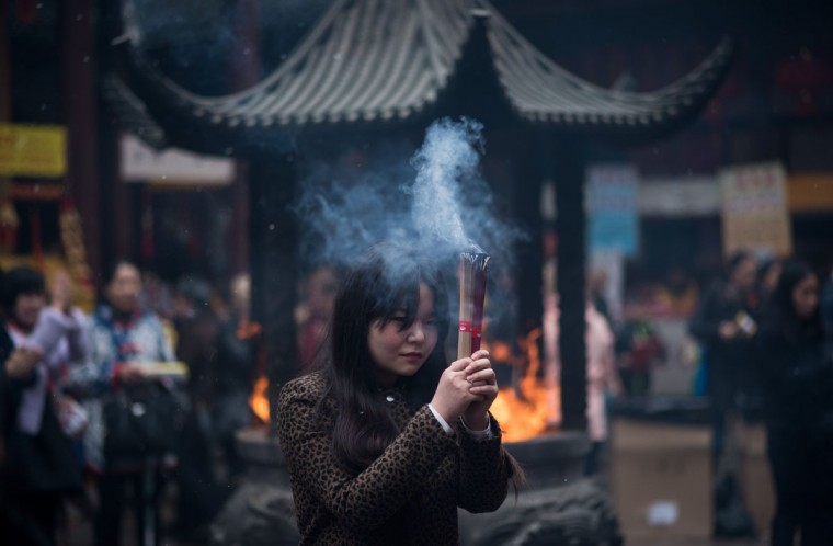 A woman burns incense as she prays for good fortune at the Jade Buddha Temple on the third day of the Chinese Lunar New Year in Shanghai on February 21, 2015. (JOHANNES EISELE/AFP/Getty Images)