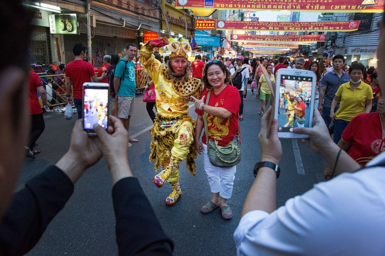 A woman poses with a costumed man during Chinese New Year on February 19, 2015 in Bangkok, Thailand. February 19 marks the first day of the Chinese lunar calendar and is celebrated amongst Bangkok's significant ethnically Chinese population. (Photo by Taylor Weidman/Getty Images)