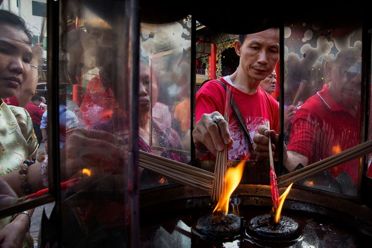 Locals light incense at a Chinese-style temple during Chinese New Year on February 19, 2015 in Bangkok, Thailand. February 19 marks the first day of the Chinese lunar calendar and is celebrated amongst Bangkok's significant ethnically Chinese population. (Photo by Taylor Weidman/Getty Images)