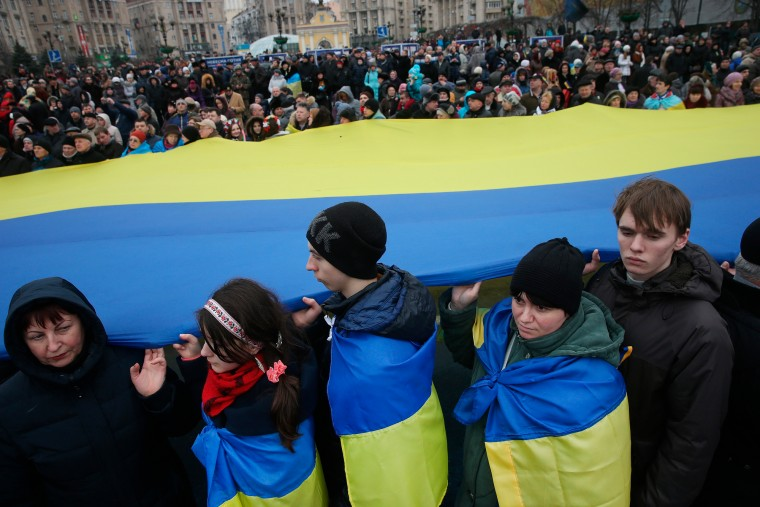 People hold up a giant Ukrainian flag following ceremonies marking the first anniversary of the Maidan revolution that led to the ouster of Ukrainian President Viktor Yanukovich one year ago at Maidan Independence Square in Kiev, Ukraine. (Sean Gallup/Getty Images Europe)