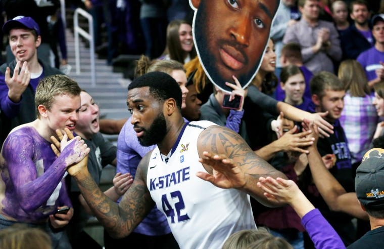 Kansas State forward Thomas Gipson (42) makes his way around Bramlage Coliseum during an NCAA college basketball game in Manhattan, Kan., to celebrate with fans after Kansas State upset #12 Iowa State 70-69. Fans were not allowed on the court after last week's game when Kansas State fans rushed the court. (Bo Rader//The Wichita Eagle/Associated Press)