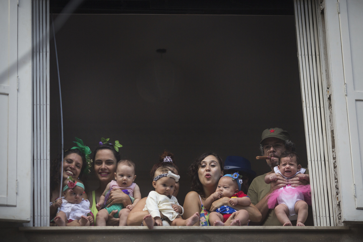 "People and babies wearing carnival costumes watch the 'Ceu na Terra', or Heaven on earth, carnival parade from the window of a house in Rio de Janeiro Brazil. Rio's over-the-top Carnival is the highlight of the year for many local residents. Hundreds of thousands of merrymakers are beginning to take to the streets in open-air ""blocos"" parties. (Felipe Dana/Associated Press)"