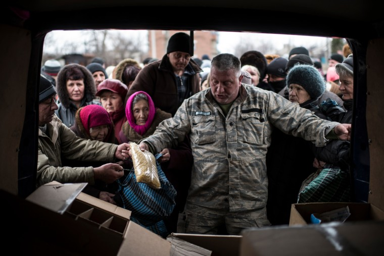 A volunteer gives humanitarian aid to local residents in Popasna, eastern Ukraine. The recent pullback of some weapons from the line separating government and rebel forces in Ukraine seems to have boosted the prospects for peace, although both sides are warning of their readiness to resume fighting if necessary. (Evgeniy Maloletka/Associated Press)