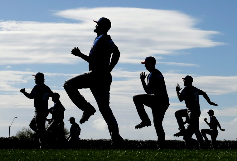 Texas Rangers players warm up during spring training baseball practice in Surprise, Ariz. (Charlie Riedel/AP)