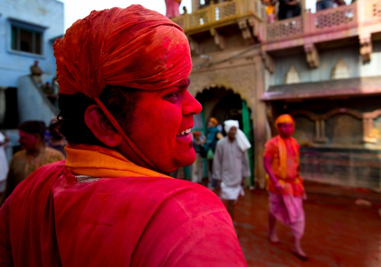 An Indian villager from Nandgaon waits for the arrival of villagers from Barsana during Lathmar holi festival, in Nandgaon, India. During Lathmar Holi the women of Nandgaon, the hometown of Krishna, beat the men from Barsana, the legendary hometown of Radha, consort of Hindu God Krishna, with wooden sticks in response to their teasing as they depart the town. (Saurabh Das/Associated Press)