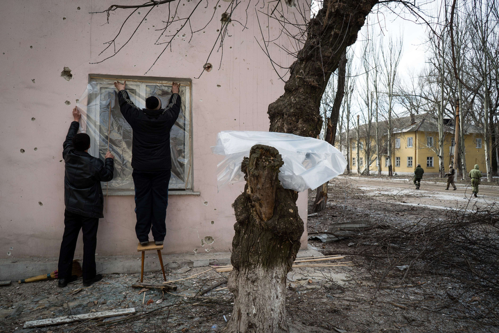 Residents fix plastic sheeting to replace a broken window in the eastern Ukrainian town of Vuglegirsk in the Donetsk region. Kiev accused pro-Russian Ukrainian separatists of massing forces for fresh offensives, with seven civilians and five soldiers killed in the latest fighting in the east. (Andrey Borodulin/AFP-Getty Images)
