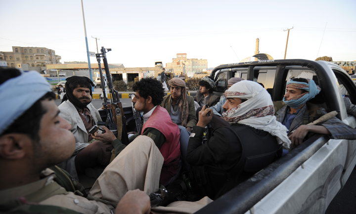 "Houthi Shiite fighters chew qat leaves, an amphetamine-like stimulant, as they ride in a pickup while guarding outside a sports stadium during a rally in Sanaa, Yemen. A group of Gulf countries denounced the Shiite rebel takeover of Yemen as a ""coup"" Saturday, calling for the United Nations to take action as thousands demonstrated in the streets against their power grab. (Hani Mohammed/Associated Press)"