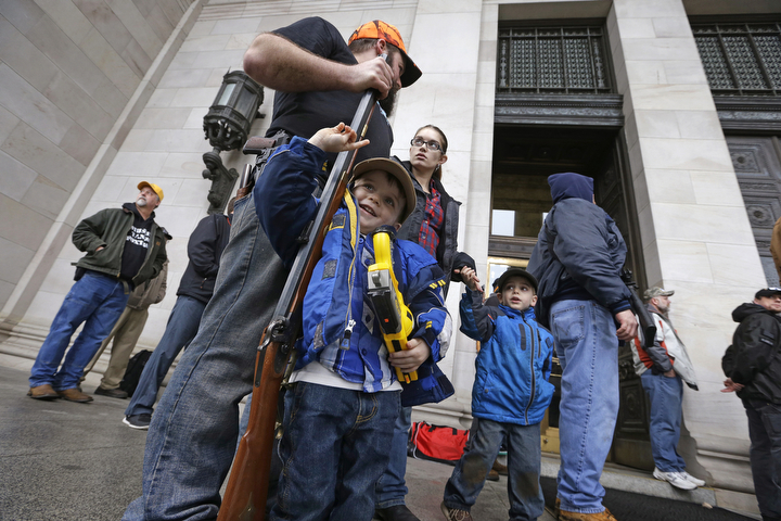 Trystan Olson, 4, of Spokane, Wash., holds a toy gun as he leans into the barrel of the rifle of his father, Erik Olson, during a rally by gun-rights advocates at the state capitol in Olympia, Wash. Approximately 50 demonstrators, including a half-dozen small children, protested rules that prohibit openly carrying guns into the House and Senate viewing galleries. (Elaine Thompson/Associated Press)