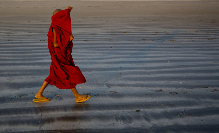 A novice Buddhist monk rearranges his robe as he walks on the beach in Ngwe Saung in western Ayeyarwady division, Myanmar. (Gemunu Amarasinghe/Associated Press)