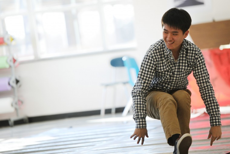 John Oh, 16, a junior and co-captain of the Mt. Hebron Break Dance team, gets up and laughs after taking a spill in the school cafeteria, Tuesday, Feb. 3, 2015. The team has a staff advisor present in case of emergencies. (Jon Sham/BSMG)