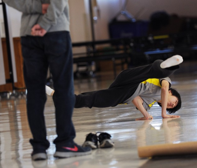 A teammates watches Mt. Hebron senior Ye Hwan Lee, 18, as he elevates himself and spins while practicing a break dancing move in the cafeteria, Tuesday, Feb. 3, 2015. (Jon Sham/BSMG)